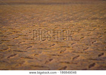 Pattern of old rusty diamond plate steel in oblique view.