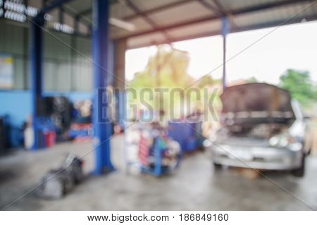 Blurred picture of car service with cars being under maintenance and technicians for background