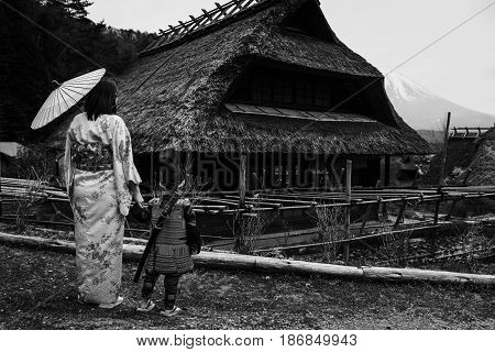 Samurai child and Japanese Kimono mother at Saiko Iyashi no Sato Nenba former farming village near Mt. Fuji Japan. Black and white process