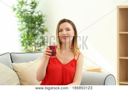 Beautiful woman with glass of fresh juice at home