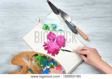 Woman painting flowers with oil paints