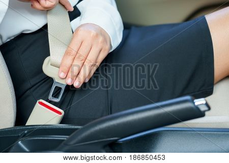 Business woman fastening seat belt in car before driving