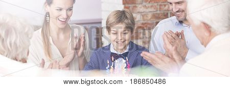 Happy family clapping their hands at boy's birthday party