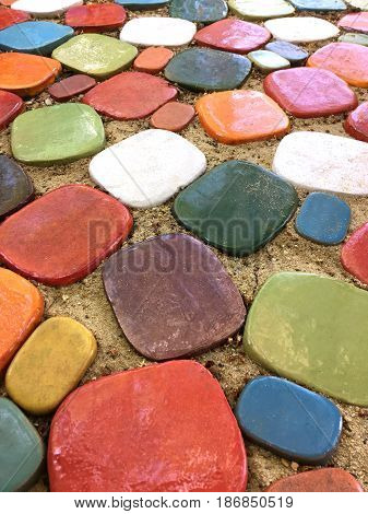 Colorful ceramic floor tiles on sand for garden decoration.