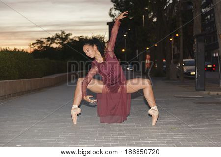 latin young female dancer performing a ballet pose in the middle of the street