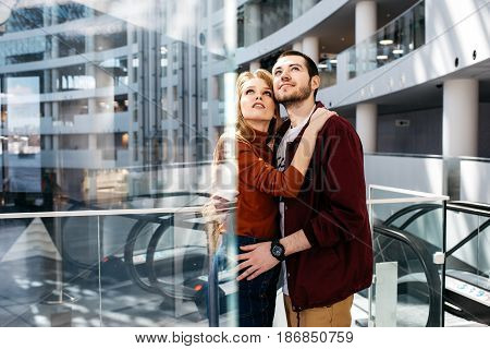 Young and handsome man and woman embrace and look up, stand inside modern business center