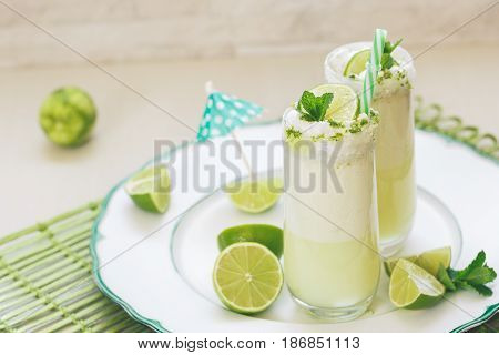 Refreshing  Brazilian lemonade or limeade in two sugar rimmed glasses,  decorated with lime slices and mint . Macro, selective focus, blank space