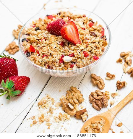 Oatmeal porridge with blueberries, strawberries, nuts and muesli on wooden table. Flat lay. Top view.