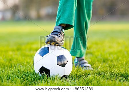 Close-up of feet and legs of little kid boy of 4 playing soccer with football on field, outdoors. Active child making sports with kids or father, Smiling happy preschool boy having fun in summer.