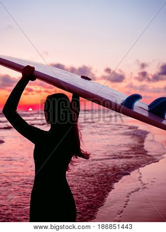 Surf girl with long hair go to surfing. Silhouette of a woman with surfboard on a beach at sunset or sunrise. Surfer and ocean
