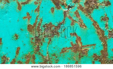 Rusty and corroded metal surface with peeled cyan paint. Grungy texture and background.