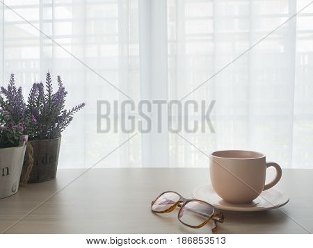 wood table with coffee cup lavender flowerpot and eyeglasses on beautiful white drape window texture background at living room.
