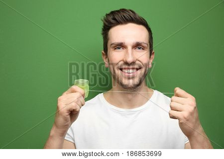 Young handsome man using dental floss on color background