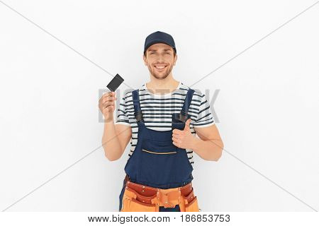 Handsome worker with business card on white background