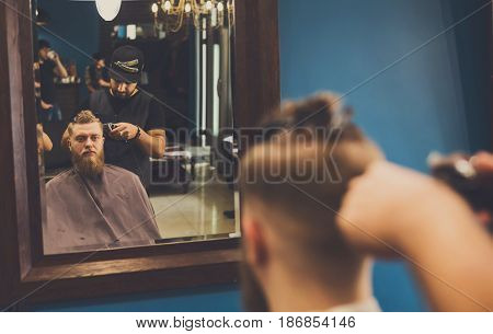 Man getting haircut by hairstylist at barbershop. Stylish barber and client in mirrow