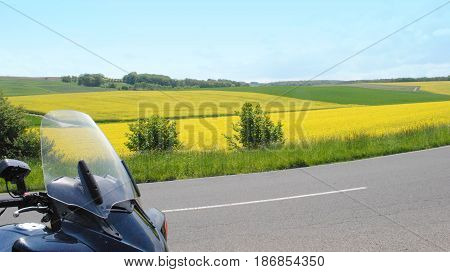 Riding with bike on a road between the fiels