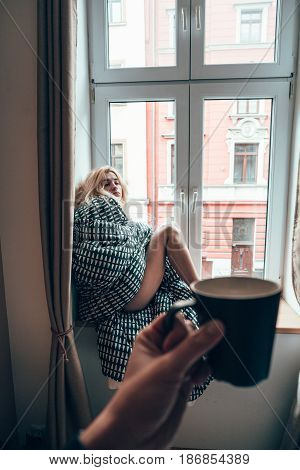 girl sitting on a window in a blanket, someone is carrying a drink