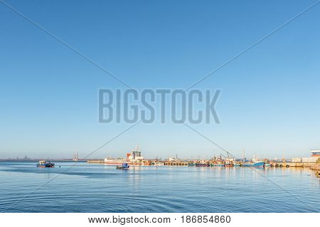 SALDANHA BAY SOUTH AFRICA - APRIL 1 2017: Several ships at sunset at a pier in Saldanha Bay a town in the Western Cape Province