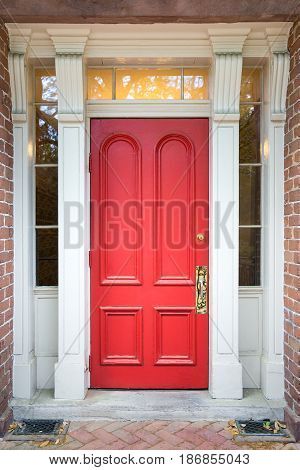 Red door framed by white columns side windows and set in red brick. Classic look with warm lighting.