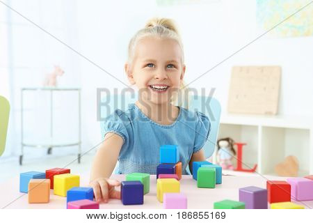 Cute little girl playing with colorful cubes at home