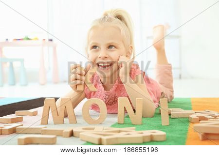 Cute little girl and word MONI composed of wooden letters on floor at home