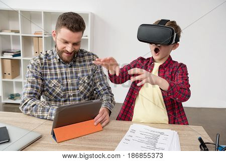 Businessman With Boy Wearing Virtual Reality Glasses At Home Office