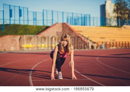 Confident woman in starting position ready for running. Female athlete about to start a sprint looking away.