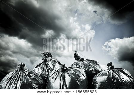 Black garbage bags and stormy sky outside. Apocalypse and pollution concept.