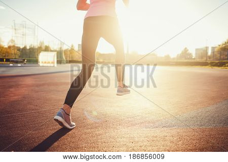 Runner athlete running on road. Woman fitness sunset jogging workout.