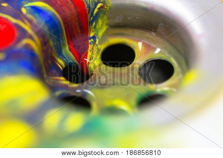 Abstract color paint flow in to the metal sink drain as homework hobby craft painting craftsmanship cleaning creativity concept background