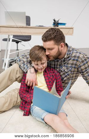 Businessman Freelancer Reading Book With Son At Home Office