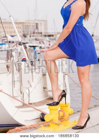 Power of woman fashion clothing feminism concept. Woman in short blue dress and high heels standing one leg on yellow marina bollard presenting her shoes.
