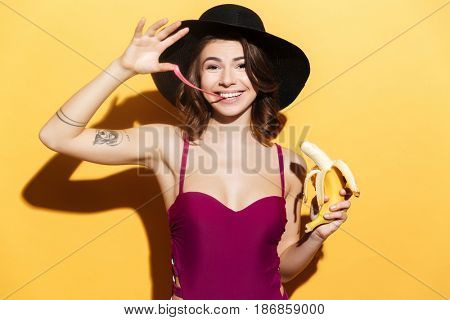 Portrait of a happy playful girl in beachwear chewing bubble gum and holding banana isolated over yellow background