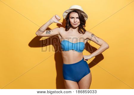 Image of sad young woman in swimwear isolated over yellow background. Looking at camera and showing thumbs down.