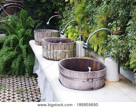 Wooden outdoor sinks with green plant in front of toilet in the park.