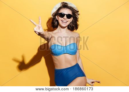 Image of happy young lady in swimwear isolated over yellow background. Looking at camera showing peace gesture.