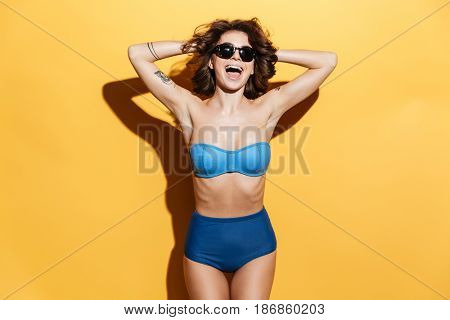 Picture of cheerful young woman in swimwear isolated over yellow background. Looking at camera.