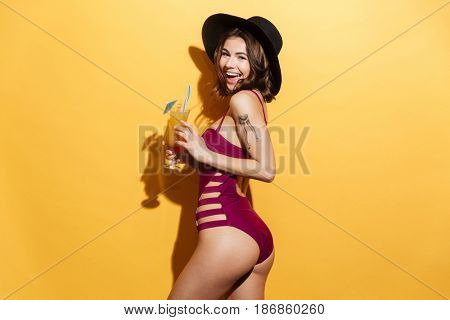 Portrait of a happy smiling young woman in beach hat and swimsuit holding cocktail and looking at camera isolated over yellow background
