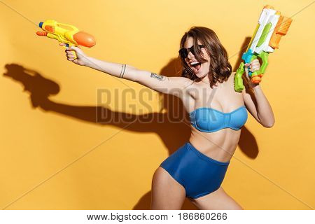 Photo of happy screaming woman in swimwear isolated over yellow background holding toys water gun. Looking aside. poster