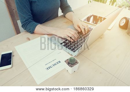 wood office table with young asian woman using laptop and resume information tablet cell phone clock at home office. concept of job search online. view form front office table.