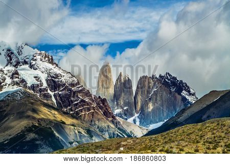 Summer in the south of Chile. The famous Torres rocks in Torres del Paine National Park. Hurricane wind carries thunderclouds. The concept of extreme and active tourism