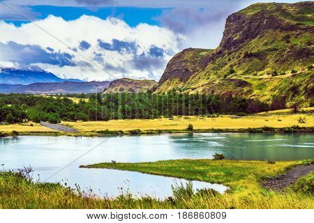 Summer in the south of Chile. Torres del Paine National Park. Rio Paine - a quiet river flow among the picturesque hills. The concept of extreme and active tourism