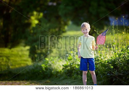 happy smiling little boy standing with american flag celebrating 4th of july