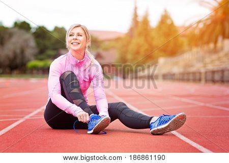 young attractive woman tying shoelaces before or after training enjoying time after good workout sun flare