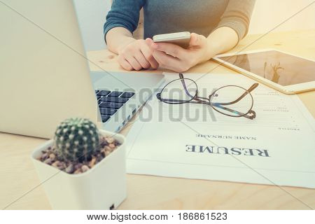 wood office table with human hand hold smartphone tablet cell phone with resume information laptop and cactus flower on pot. concept of job search online. view form front office table.