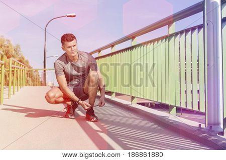 Full length of sporty man tying shoelace on bridge
