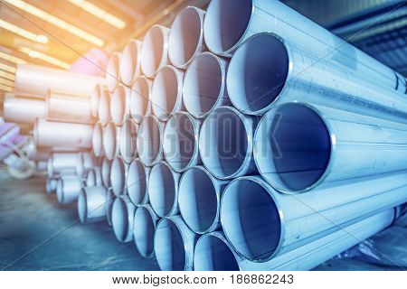 Stainless steel pipes on warehouse in steel construction industry. Selective focus. Blue tone