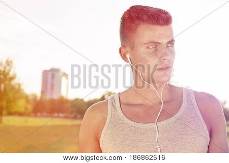 Male jogger looking away while listening music in park