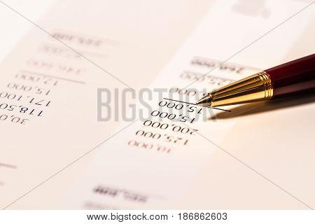 Finance number focus, data , pen reviewing financial figures