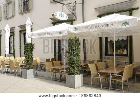 GRAZ, AUSTRIA - MARCH 20, 2017: Sun umbrellas on tables at the exterior of a bar in Graz the capital of federal state of Styria Austria.
